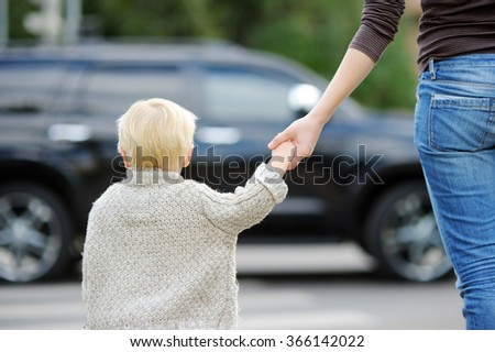 Mother and toddler son crossing the street on the crosswalk