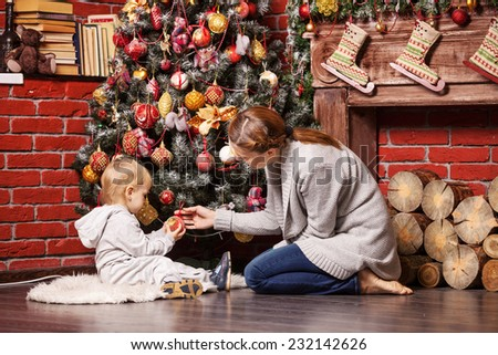 Mother and toddler son holding Christmas ball on Christmas tree at home - stock photo