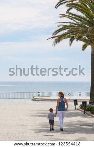 Mother and toddler son holding hands and walking on the boulevard - stock photo