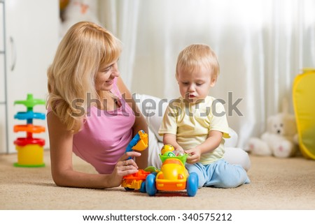 Mother and toddler son playing with toy car on nursery floor - stock photo