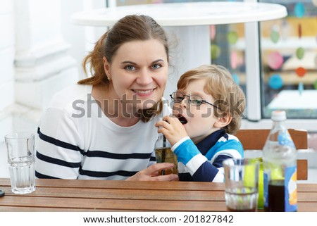Mother and toddler son relaxing in outdoor restaurant - stock photo