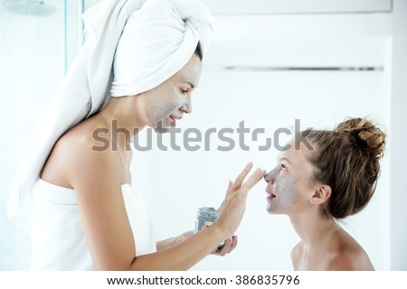 Mother and tween daughter make a clay facial mask, family skin care in the bathroom - stock photo