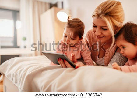 Mother and two baby girls looking at a tablet