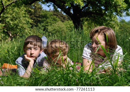 mother and two boys laying in the green grass and having fun - stock photo