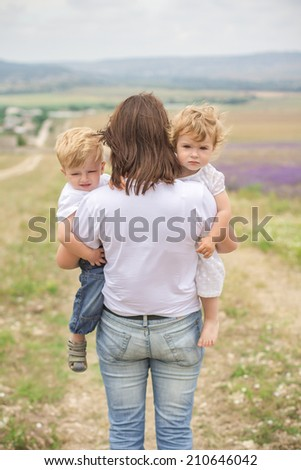 mother and two children cry in a field - stock photo