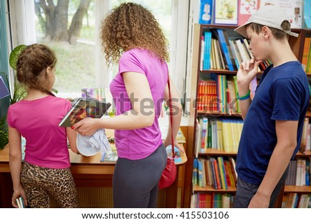 Mother and two children explore books in children library.