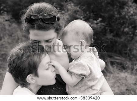 mother and two children in loving embrace, black and white - stock photo