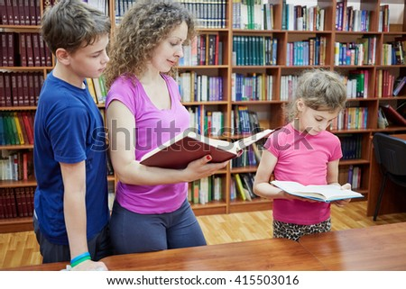Mother and two children stand at table reading books in library. - stock photo
