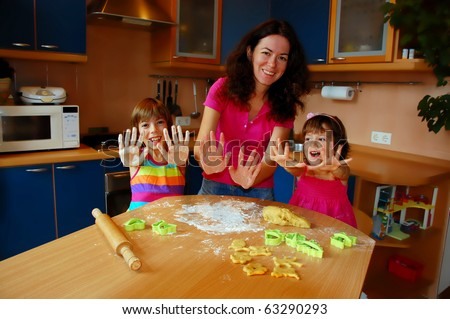 Mother and two daughters baking together in the kitchen - stock photo