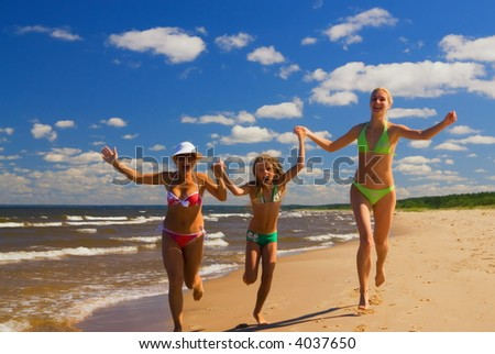 Mother and two daughters running on a beach near the water - stock photo