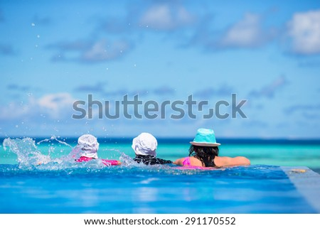 Mother and two kids enjoying summer vacation in luxury swimming pool - stock photo