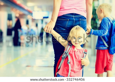 mother and two kids walking in the airport, family travel - stock photo