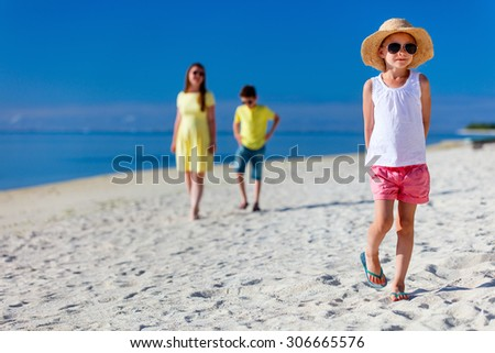 Mother and two kids walking on a tropical beach enjoying summer vacation - stock photo