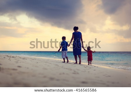 mother and two kids walking on sunset beach