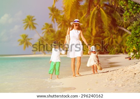 mother and two kids walking on tropical beach, family vacation - stock photo