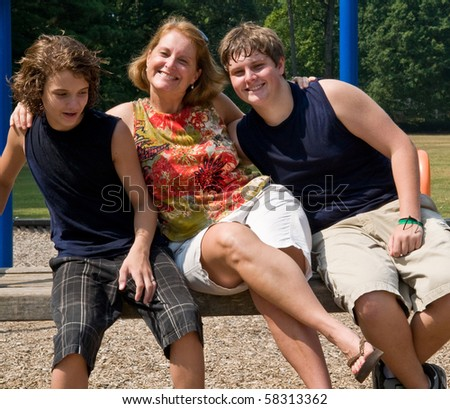mother and two sons horsing around on a playground bench - stock photo