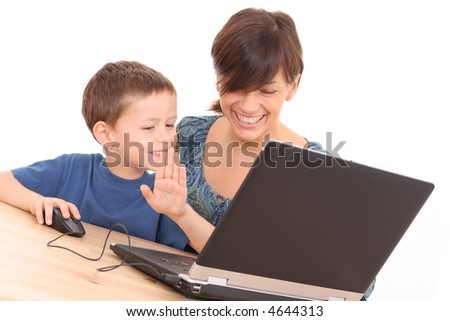 mother and 5-6 years old son having fun with computer game isolated on white