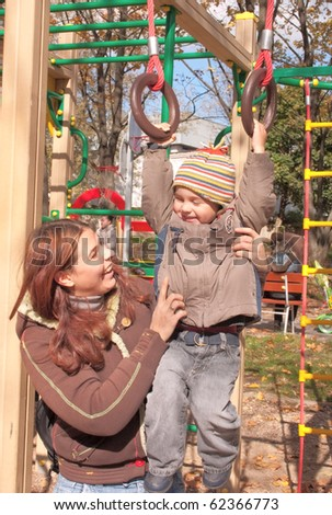 Mother and 2 years old son on the playground. - stock photo