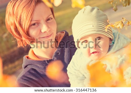 Mother and young baby walking in autumn garden. Image toned with vintage filter - stock photo
