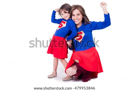 Mother and young daughter happily interacting together, both dressed in superman outfits with red skirts, all white studio background