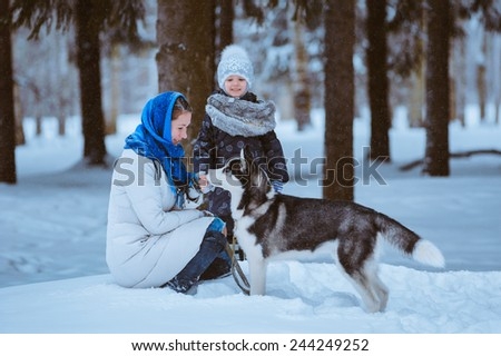 mother and young daughter playing with husky dog, winter time - stock photo
