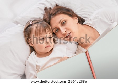 Mother and young daughter reading book on couch at home - stock photo