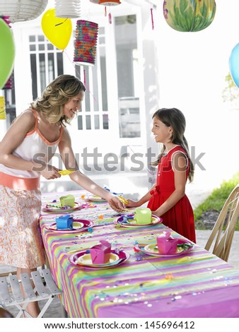 Mother and young daughter setting outdoor table for birthday party - stock photo
