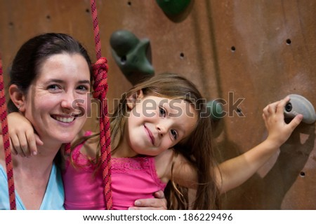 Mother and young daughter together in indoor climbing gym. - stock photo