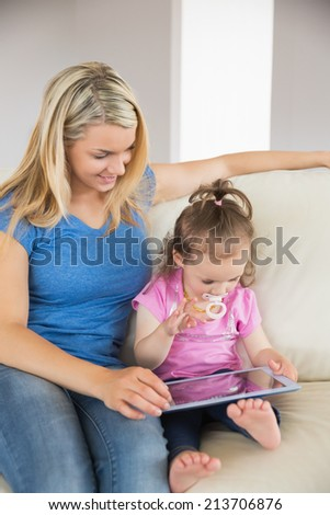 Mother and young daughter using digital tablet on couch at home
