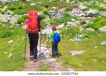 Mother and young kid carrying backpacks on sunny mountain trail - stock photo