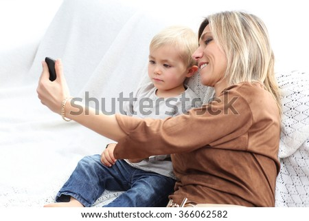 mother and young son playing with electronics