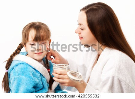 mother applying cream on her daughter's face in bed at home