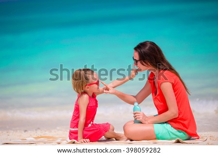 Mother applying sun protection cream to her daughter at tropical beach - stock photo