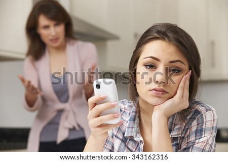 Mother Arguing With Daughter Over Use Of mobile Phone - stock photo