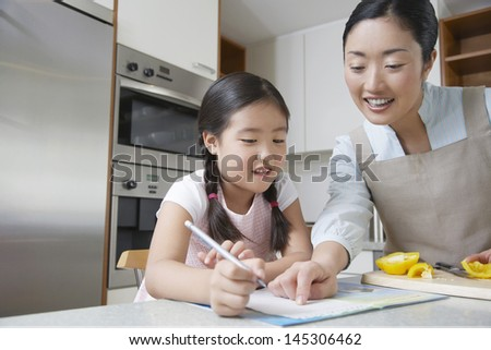 Mother assisting girl with her homework in the kitchen - stock photo