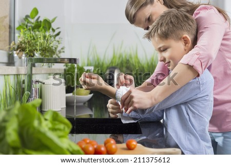 Mother assisting son in folding sleeves while washing hands in kitchen - stock photo