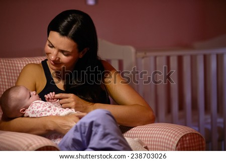 Mother At Home Cuddling Newborn Baby In Nursery - stock photo