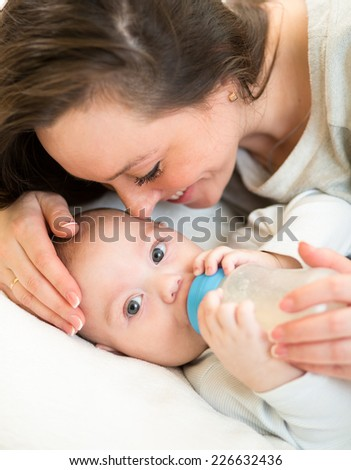 mother at home feeding baby with a milk bottle - stock photo