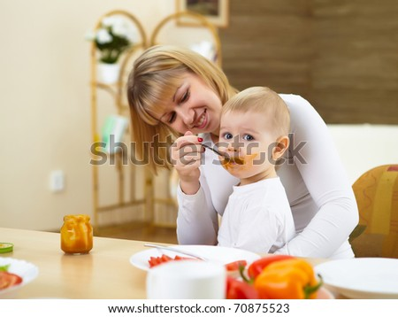 mother at home having meal together with a baby - stock photo