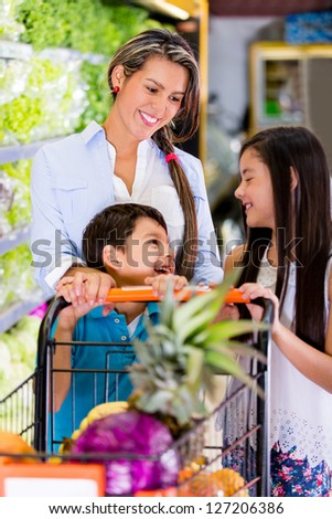 Mother at the supermarket with her two kids - stock photo