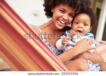 Mother bonding with young son sitting in a hammock, portrait - stock photo
