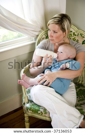 Mother bottle-feeding her seven month old baby - stock photo