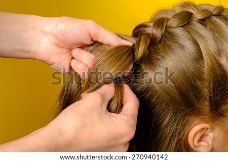 Mother braiding French braid her daughter - stock photo