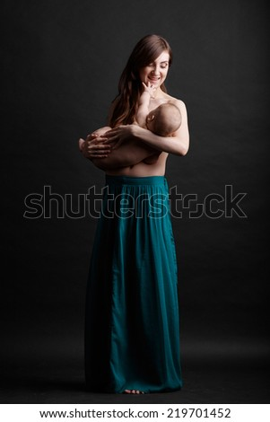Mother breast feeding her infant studio shot - stock photo