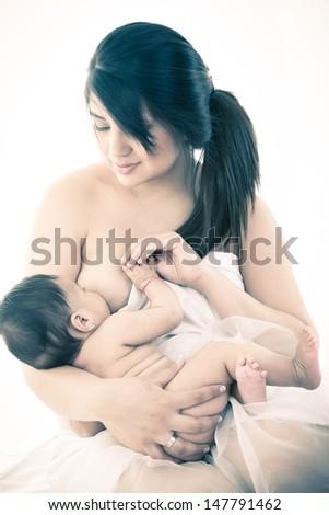 mother breastfeeding a little baby studio shot - stock photo