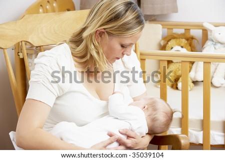 Mother Breastfeeding Baby In Nursery - stock photo