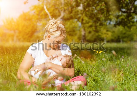 Mother breastfeeding her baby on a great sunny day in a meadow  - stock photo