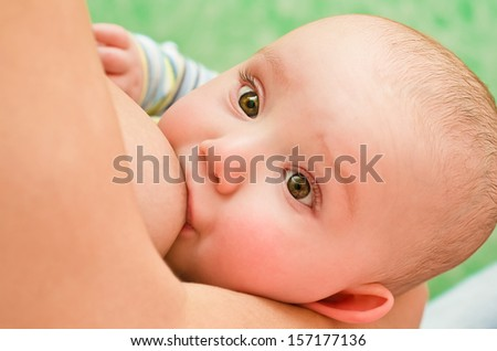 Mother breastfeeding her baby with breast milk - stock photo