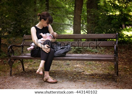 Mother breastfeeding her newborn baby girl in the park on demand, sitting on the bench under the trees, instagram style effect applied - stock photo