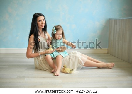 mother brunette in long dress sitting on the floor with her daughter in a blue sundress and holding a small ducklings - stock photo